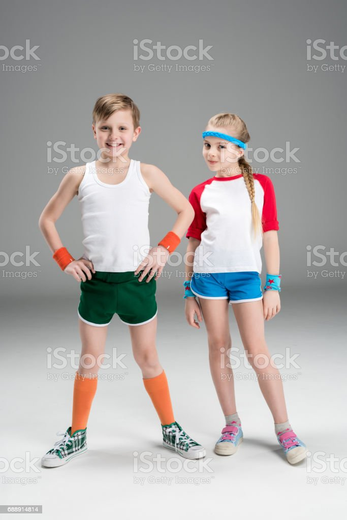 Full length view of cute smiling boy and girl in sportswear standing together isolated on grey, children sport concept stock photo