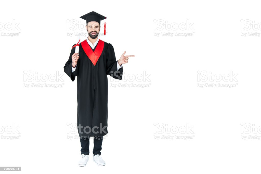 Full length view of happy young student holding diploma and pointing away with finger stock photo