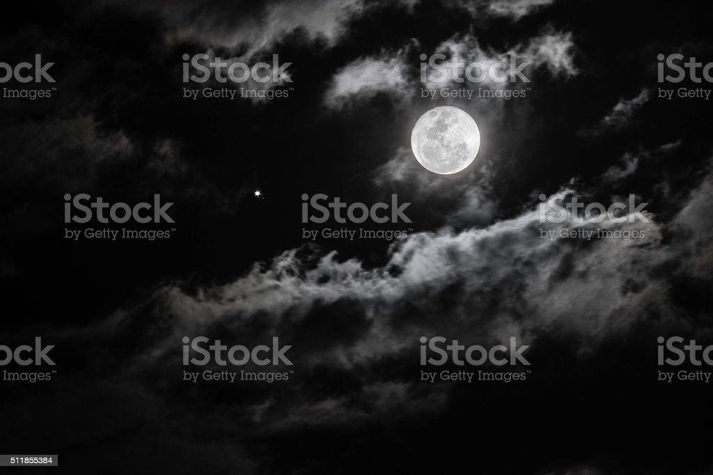 Full moon among the clouds with a star stock photo