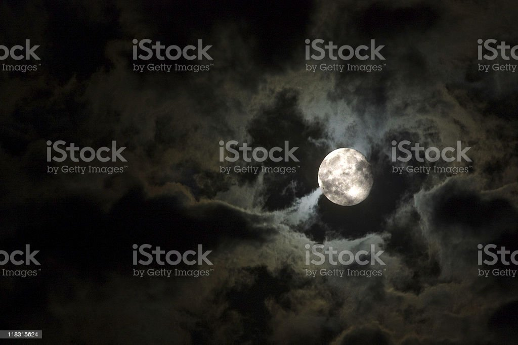 Full moon and eerie white clouds against a black sky stock photo