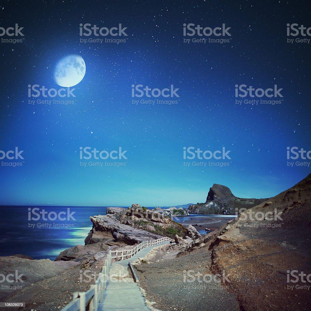 Full moon and rock coast stock photo