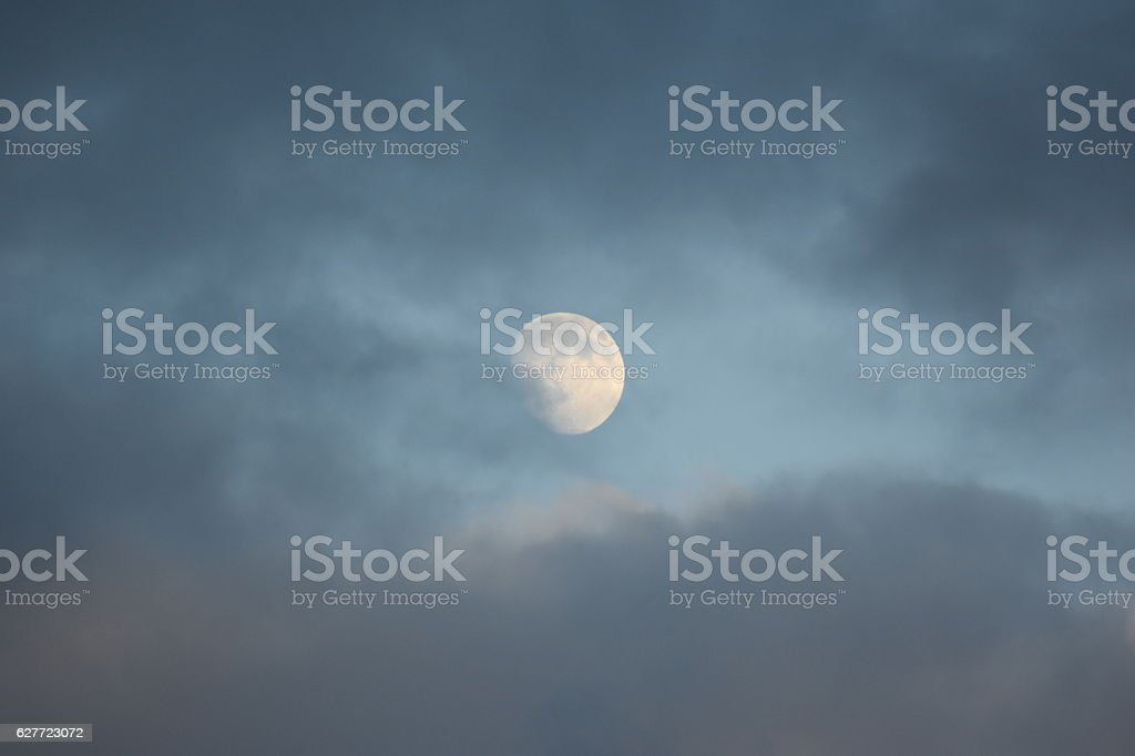 Full Moon at Dusk Blue Sky Grey Clouds stock photo