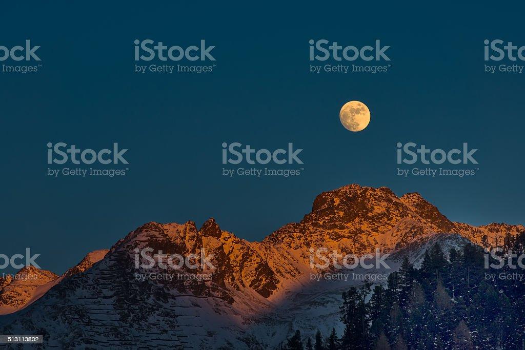 Full moon at sunset on winter mountains stock photo