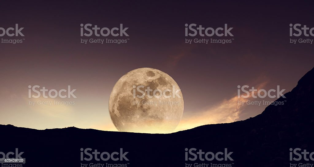 Full moon before sunrise with silhouette mountain stock photo