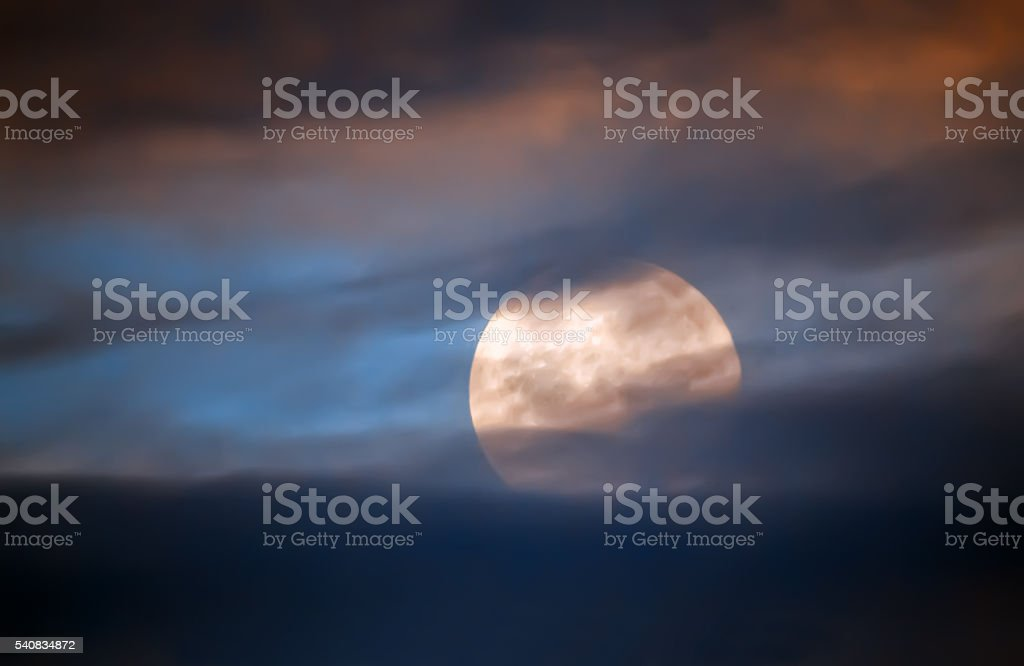 Full moon behind clouds stock photo