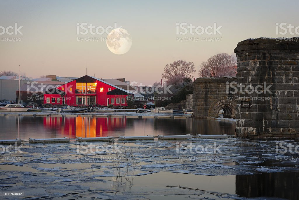 Full moon on top of rowing club in winter morning stock photo