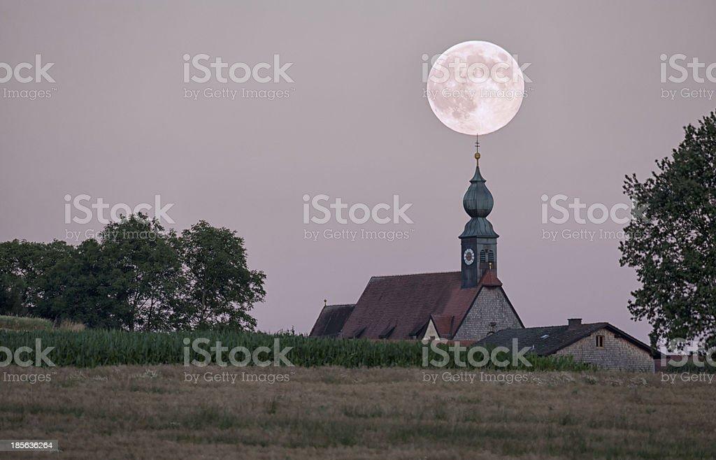 Full moon over churchtower stock photo