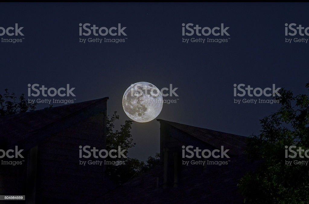 Full Moon over roof peaks at twilight stock photo