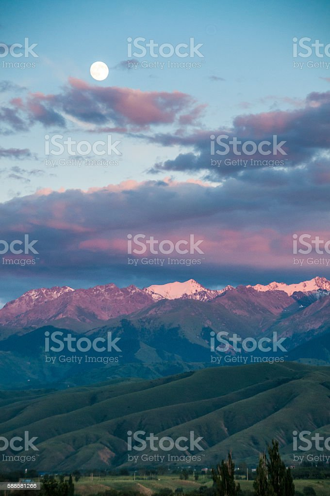 Full moon over snow peaks and foothills stock photo