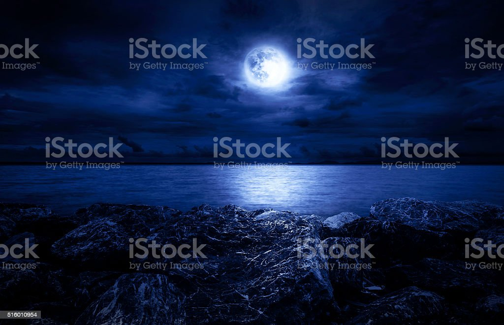 Full moon over the ocean with clouds and rocks stock photo