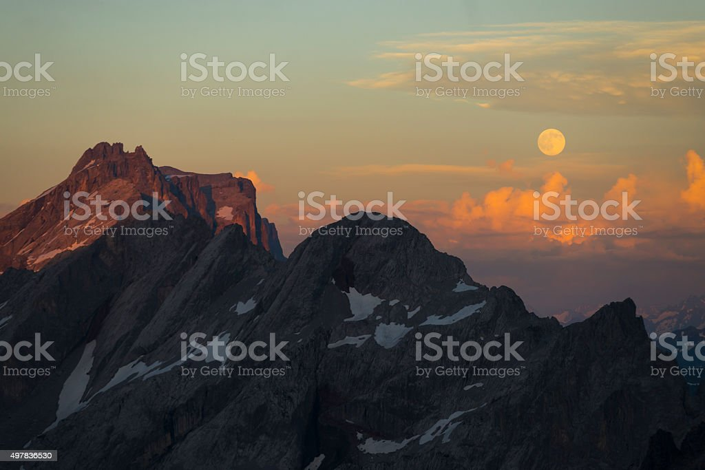 Full moon rising above mountains with clouds illuminated by sunset stock photo