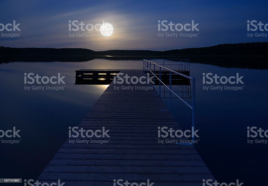 Full Moon Rising over Calm Lake with Boardwalk Dock stock photo