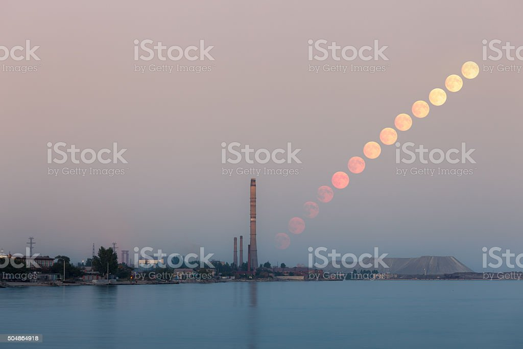 Full moon rising over industrial landscape stock photo