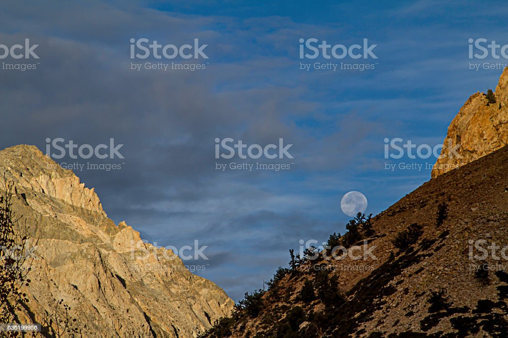 Full moon setting behind a mountain stock photo