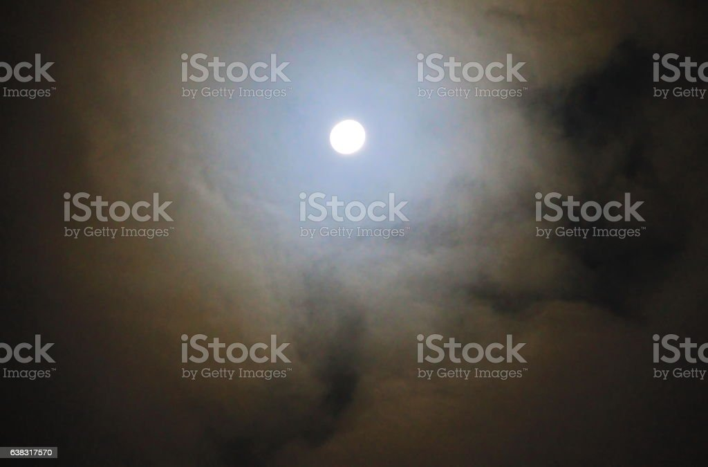 Full moon shining through the clouds stock photo