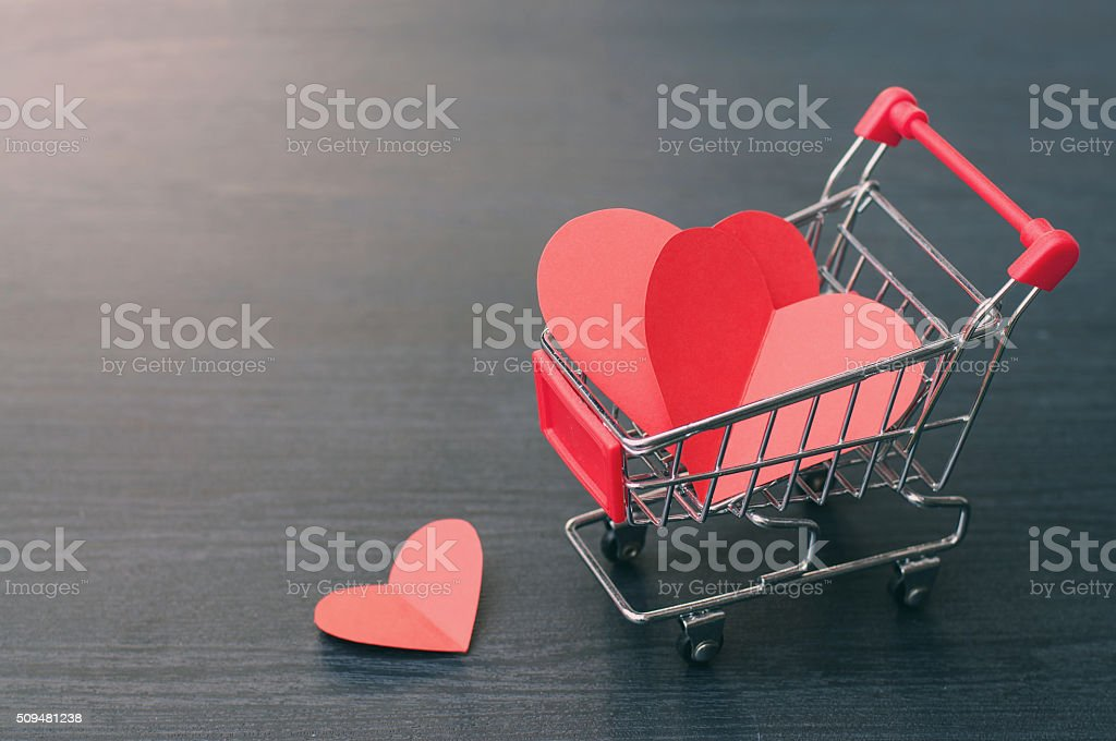 Full of hearts in the shopping cart on wooden floor stock photo