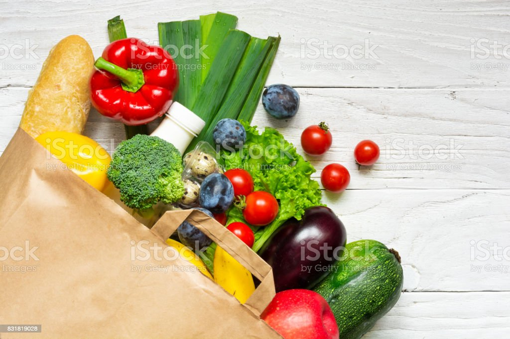 Full paper bag of different health food on white wooden background....