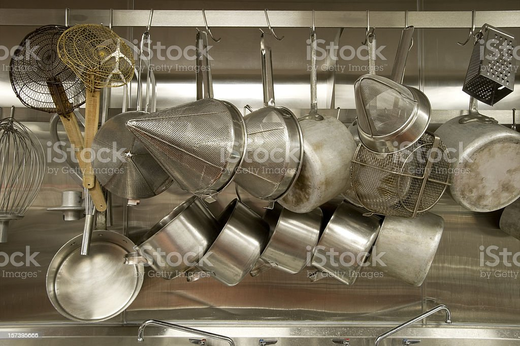 A full pot rack in a commercial kitchen  stock photo