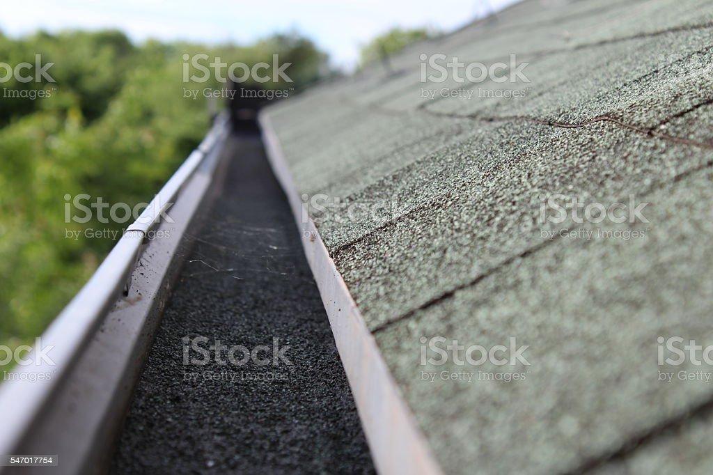 Full rain gutter on roof - Stock Image stock photo