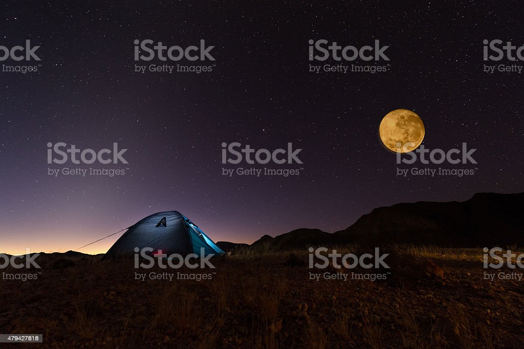 Full red moon and stars over lit tent in desert stock photo