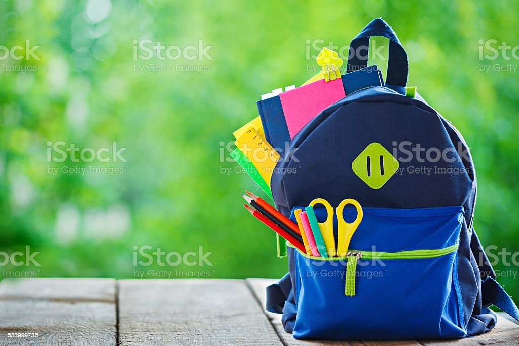 Full School backpack on wooden and nature background. stock photo