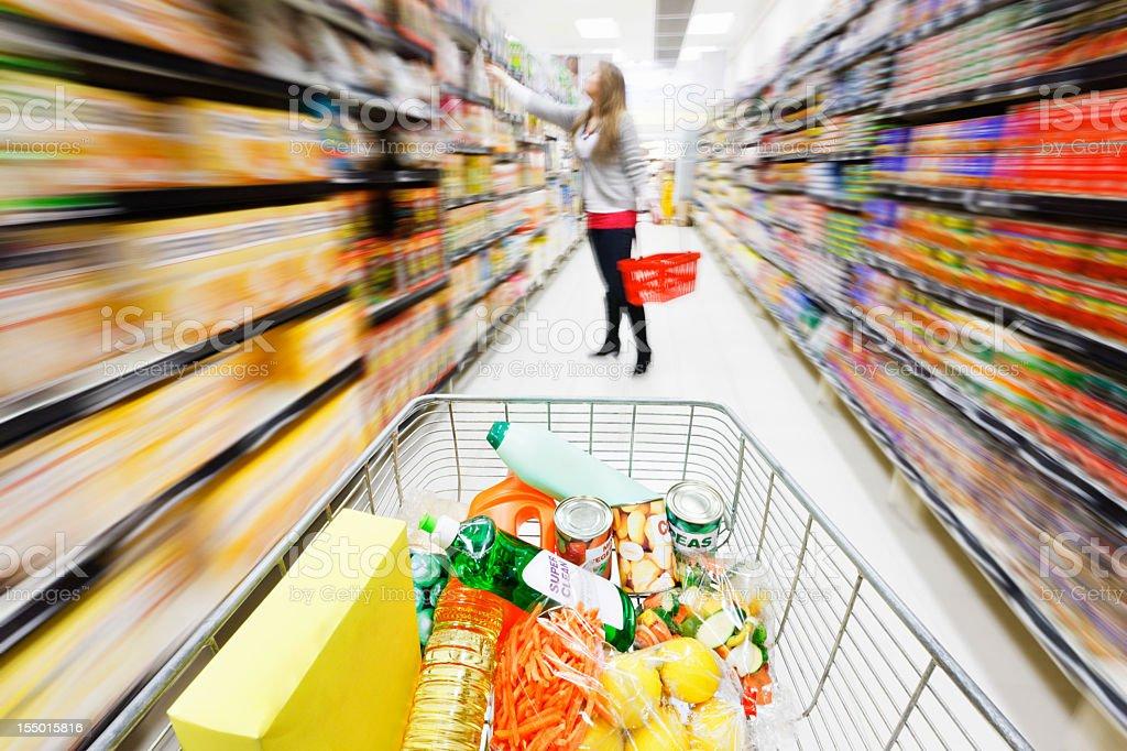 Full shopping cart speeding through supermarket with major motion blur royalty-free stock photo