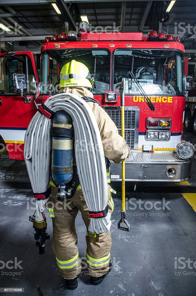 Full shot of fireman wearing full protection equipment and truck stock photo