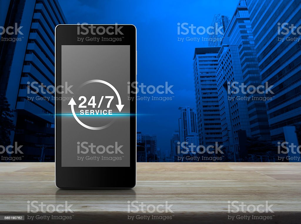 Full time service icon on phone screen on wooden table stock photo