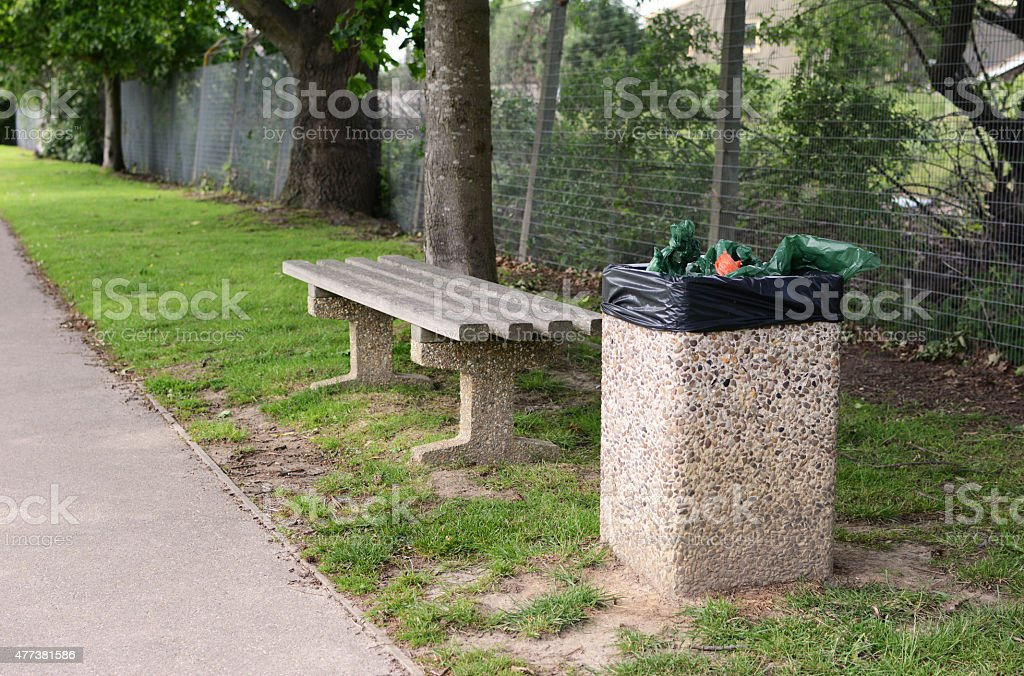 Full trash can next to empty bench stock photo