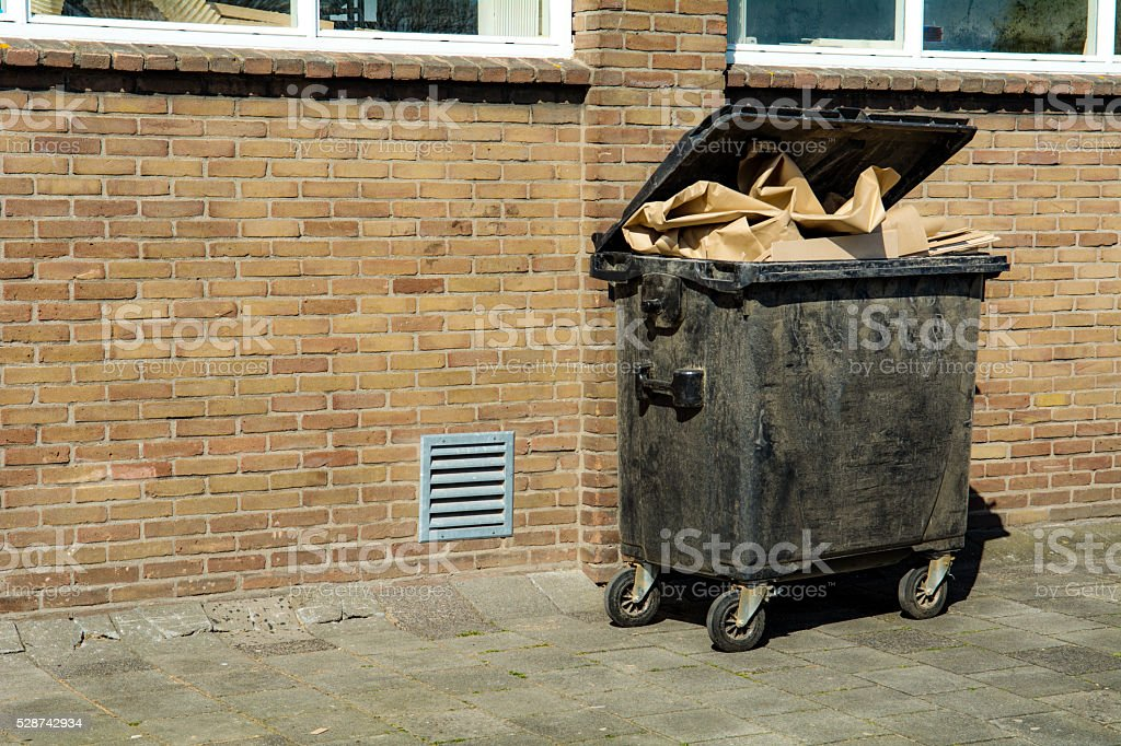 Full wheeled cardboard  recycling bin with brown boxes behind workshop stock photo