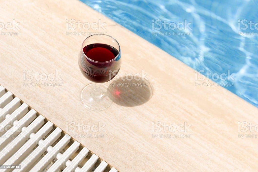 Full wine glass near the pools edge. stock photo
