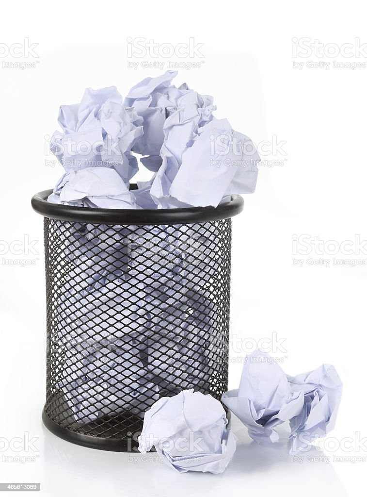 Full wire mesh trash can with crumpled paper scattered around royalty-free stock photo