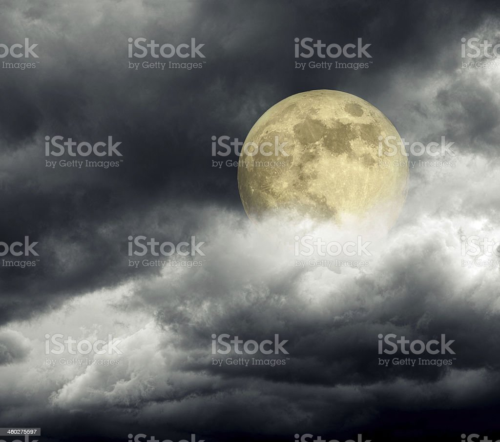 Full yellow moon above clouds at night stock photo