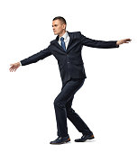 Fully concentrated businessman walking tightrope or border, isolated on white