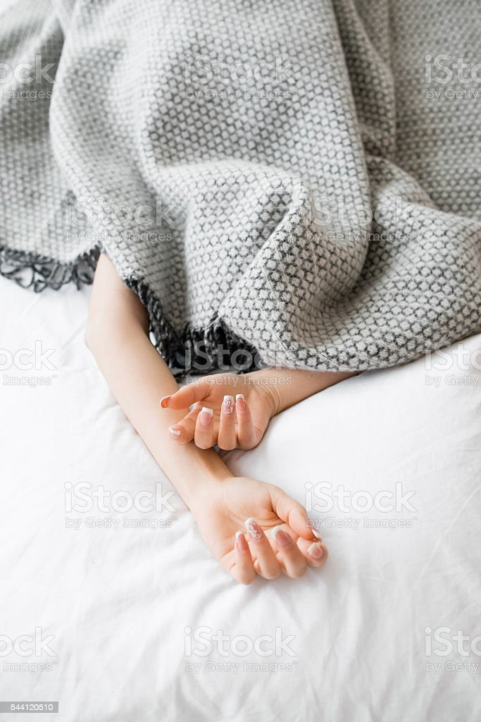 Fully covered woman except hands in bed stock photo