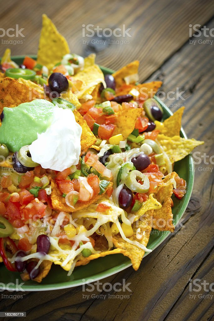 Fully loaded nachos in a green plate on a wooden table stock photo