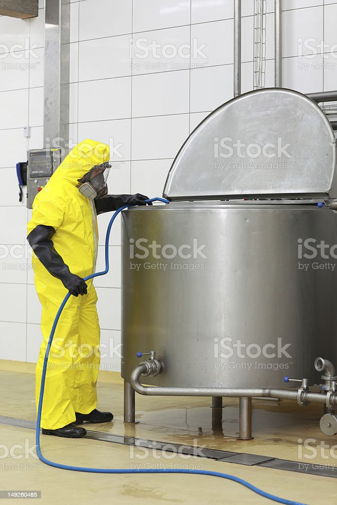 fully protected specialist with hose in at industrial tank stock photo