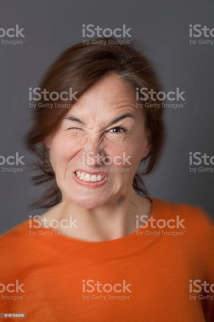 fun angry expression for winking middle aged woman, blur effects stock photo