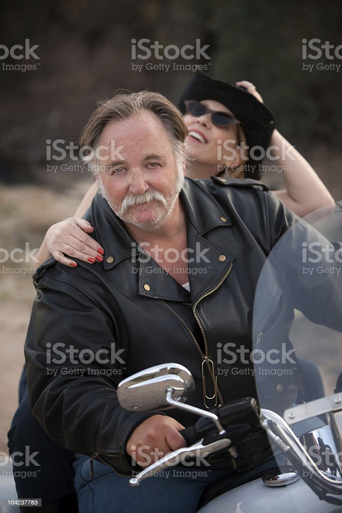Fun couple riding a white motorcycle outside royalty-free stock photo