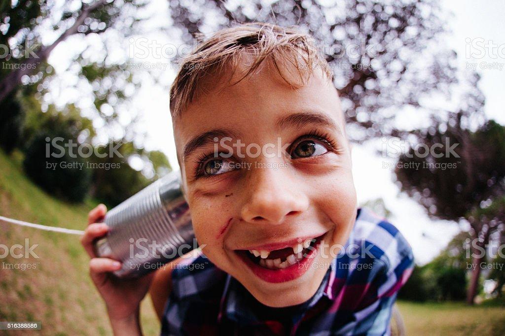 Fun fisheye shot of boy's face with tin can phone stock photo