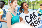 Fun friends hold 'Car Wash' sign to promote the event