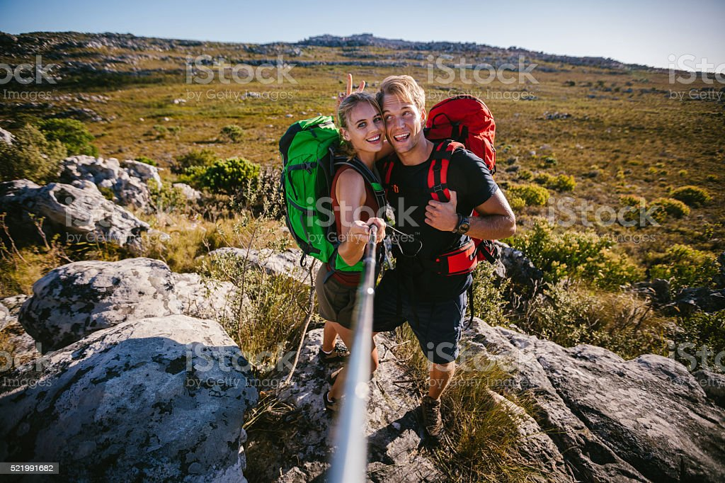 Fun friends pulling a face for selfie stick on hike stock photo