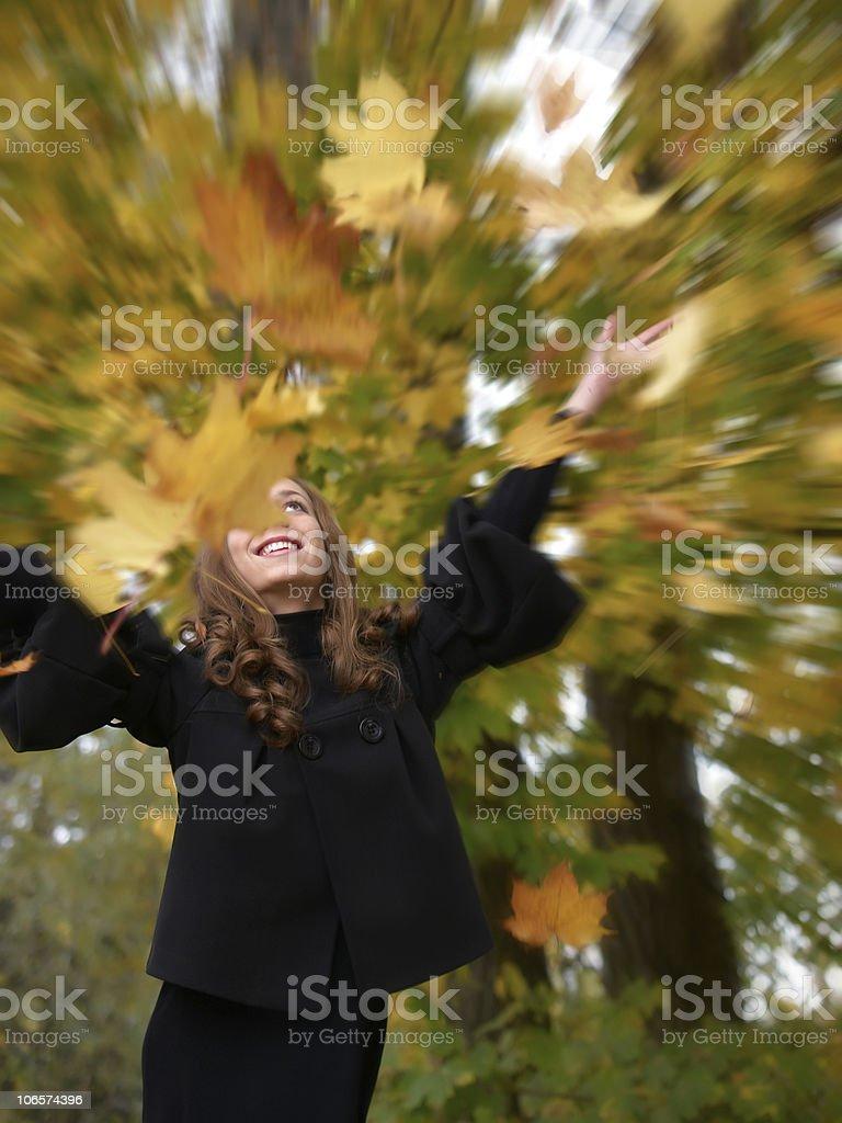Fun girl tosses fall foliage stock photo