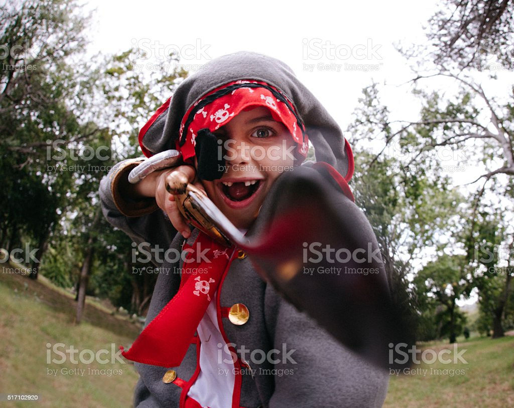 Fun Pirate boy playfully fighting with his saber in park stock photo