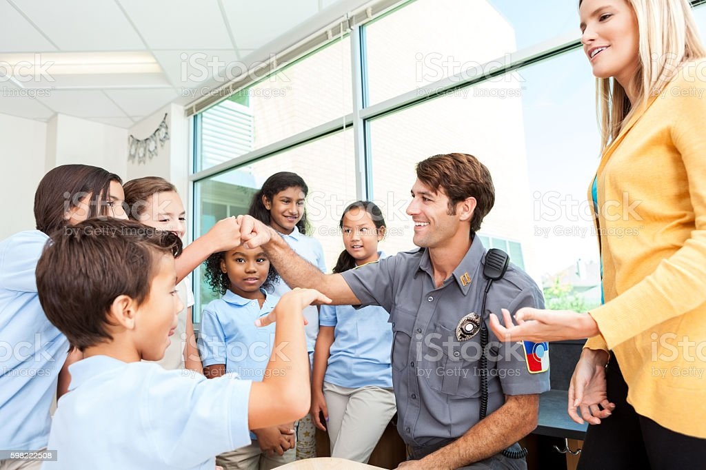 Fun police officer gives fist bumps to school kids stock photo