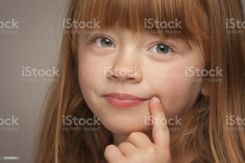 Fun Portrait of an Adorable Red Haired Girl on Grey royalty-free stock photo