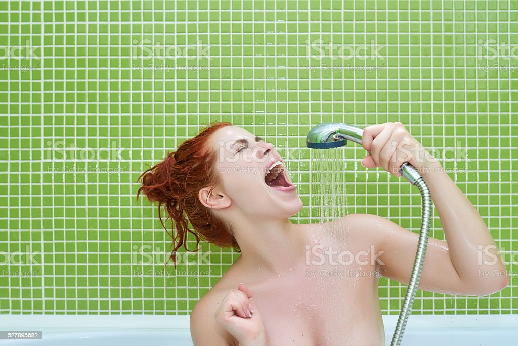 horizontal shot of funny woman singing in the shower and enjoying her...