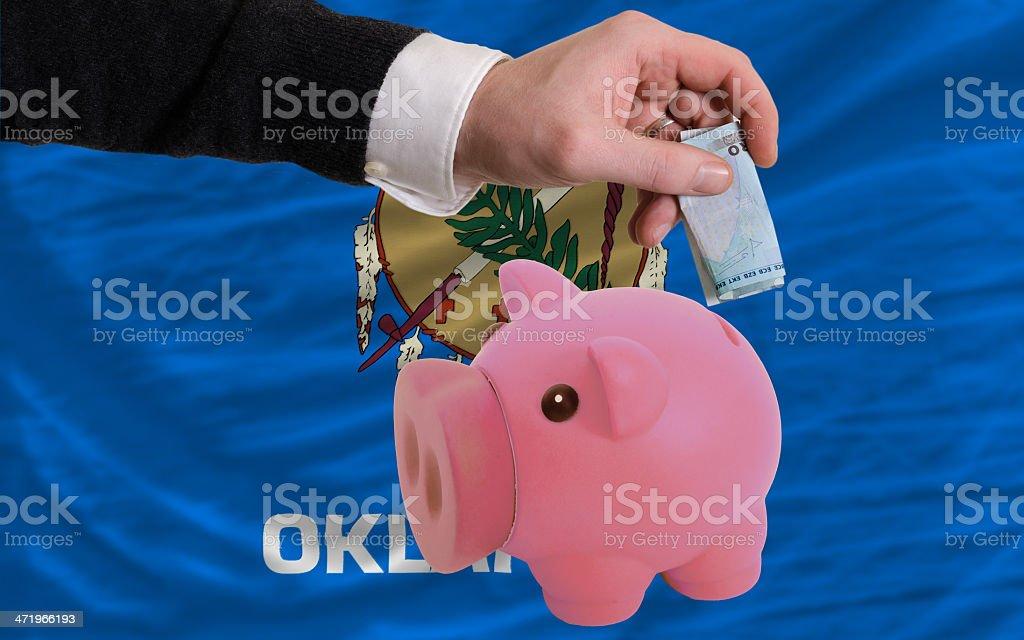 Funding euro into piggy rich bank flag of oklahoma royalty-free stock photo