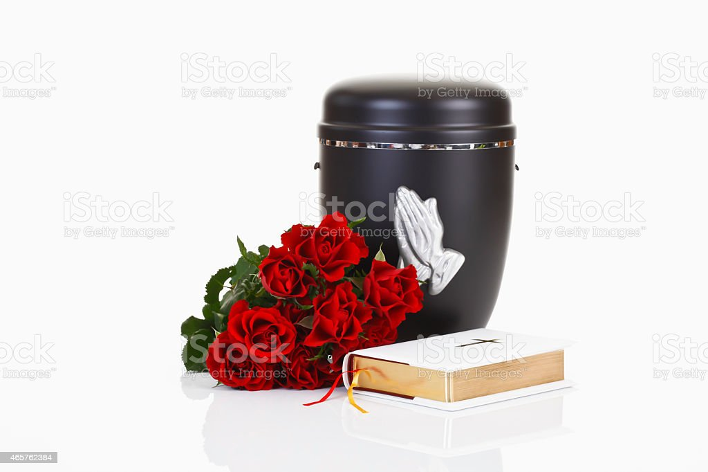 Funeral, urn with praying hands, white bible and red roses stock photo