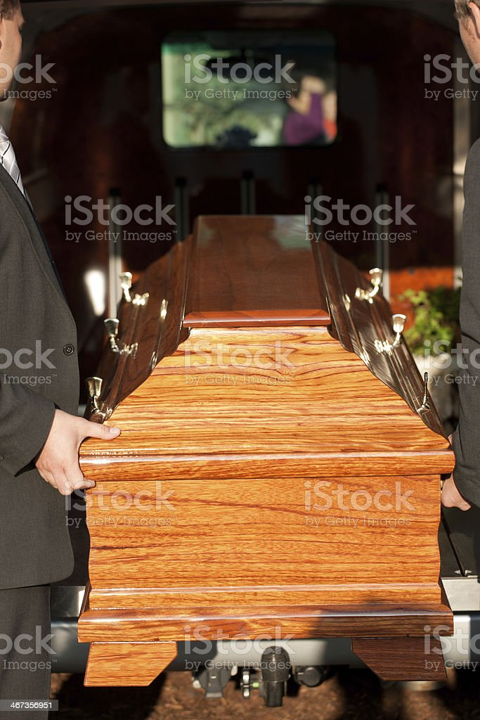 Funeral with casket carried by coffin bearer stock photo